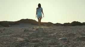 Девушка в белом платье идя к заходу солнца от камеры пустыня движение медленное видеоматериал