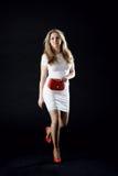 Девушка в белом платье, красных ботинках и красной сумке муфты Стоковые Фотографии RF