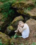 Девушка в белом платье на больших утесах с лилиями Стоковое фото RF