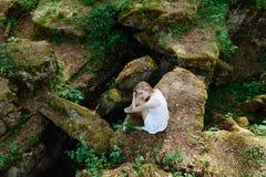 Девушка в белом платье на больших утесах с лилиями Стоковая Фотография