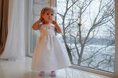 Девушка в белом платье рядом с большим окном стоковое фото rf
