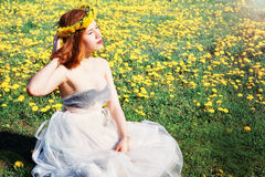 Девушка в белом платье сидя на glade одуванчиков стоковые фото
