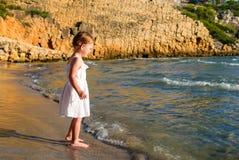 Девушка в белом платье стоя barefoot на пляже на заходе солнца Стоковые Изображения