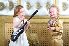 Девушка в белых гитаре игр платья и музыканте шипучки поет стоковые изображения rf