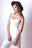 Девушка в белых одеждах и черной шляпе представляя в студии на белой предпосылке Стоковое Изображение RF