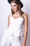 Девушка в белых одеждах и черной шляпе представляя в студии на белой предпосылке Стоковая Фотография