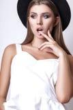 Девушка в белых одеждах и черной шляпе представляя в студии на белой предпосылке Стоковые Изображения