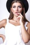 Девушка в белых одеждах и черной шляпе представляя в студии на белой предпосылке Стоковое Фото