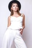 Девушка в белых одеждах и черной шляпе представляя в студии на белой предпосылке Стоковые Изображения RF