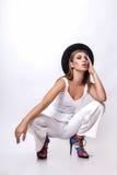 Девушка в белых одеждах и черной шляпе представляя в студии на белой предпосылке Стоковые Фотографии RF