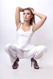 Девушка в белых одеждах представляя в студии на поле на белой предпосылке Стоковые Изображения