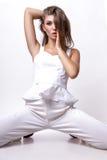 Девушка в белых одеждах представляя в студии на поле на белой предпосылке Стоковые Фото