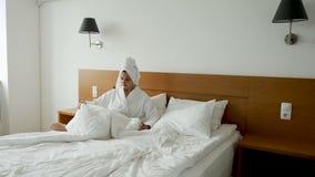 Девушка в белых падениях купального халата сток-видео