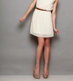 Девушка в белых пятках платья на сером цвете Стоковая Фотография