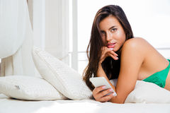 Девушка в бикини лежа на кровати с smartphone Стоковое фото RF