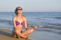 Девушка в бикини meditating на пляже Стоковые Изображения RF