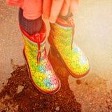 Девушка в ботинках дождя стоит в лужице Стоковые Изображения