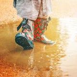 Девушка в ботинках дождя стоит в лужице Стоковая Фотография