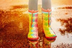 Девушка в ботинках дождя стоит в лужице Стоковая Фотография RF
