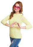 Девушка в больших розовых eyeglasses делает сердца сформировать жест, одетые джинсы и зеленый свитер представляя в студии на бело Стоковые Изображения