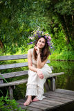 Девушка в венке сидя на склонности стенда на локтях Стоковые Фото