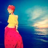 Девушка в востоковедном стиле на пляже на заходе солнца стоковые фото