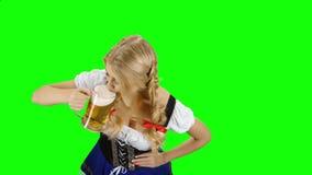 Девушка в вылизанном пиве баварского костюма выпивая от стекла и зеленый экран сток-видео