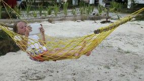 Девушка в гамаке с таблеткой на пляже видеоматериал