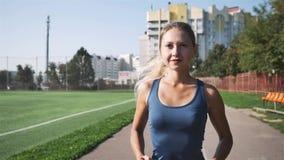Девушка в гетры делает бег через стадион