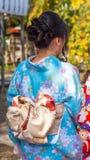 Девушка в голубом кимоно на улице города, токио, Японии вертикально Конец-вверх задний взгляд Стоковые Фотографии RF