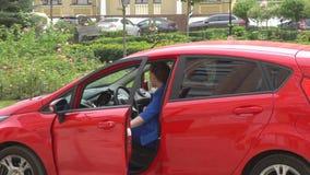 Девушка в голубом костюме приходит к парадному входу автомобиля и openes Она сидит вниз в машине и конце дверь Девушка управляет  акции видеоматериалы
