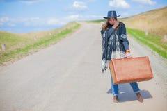 Девушка в голубых джинсах, плащпалата, черная кожаная шляпа с старым коричневым чемоданом в ее руках на дороге Стоковые Изображения RF