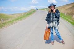 Девушка в голубых джинсах, плащпалата, черная кожаная шляпа с старым коричневым чемоданом в ее руках на дороге Стоковая Фотография RF