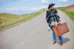 Девушка в голубых джинсах, плащпалата, черная кожаная шляпа с старым коричневым чемоданом в ее руках на дороге Стоковое Изображение