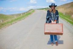 Девушка в голубых джинсах, плащпалата, черная кожаная шляпа с старым коричневым чемоданом в ее руках на дороге Стоковые Изображения