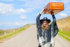 Девушка в голубых джинсах, плащпалата, черная кожаная шляпа с старым коричневым чемоданом в ее руках на дороге Стоковое Фото