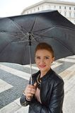 Girl in the city walking in the rain, smiling Стоковое Изображение RF