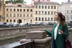 Девушка в городке, девушка в зеленом пальто смотря вверх, девушка распространила ее Хан Стоковые Изображения RF