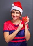 Девушка в голове santa с подарочной коробкой на серой предпосылке Стоковые Фотографии RF