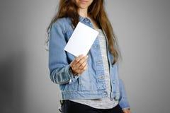 Девушка в голубой рубашке джинсовой ткани держит белую пустую часть  стоковое изображение rf