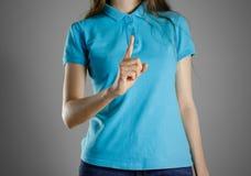 Девушка в голубой футболке указывая палец на поднимающем вверх Определяет th Стоковая Фотография RF
