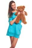 Девушка в голубом платье с изолятом плюшевого медвежонка на белой предпосылке Стоковое Фото