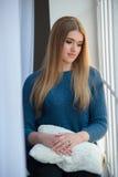 Девушка в голубом шерстяном свитере смотря окно стоковое фото rf