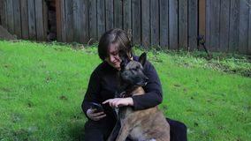 Девушка в дворе с собакой и телефоном акции видеоматериалы