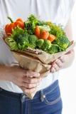 Девушка в джинсах и белой футболке держит первоначально букет свежих овощей Стоковое Изображение
