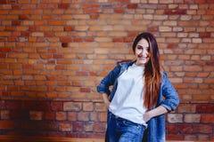 девушка в джинсах на предпосылке кирпичной стены стоковое фото
