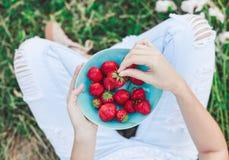Девушка в джинсах сидя в траве лета и держа плиту клубник, коленей и рук видимых Здоровый завтрак, Стоковое Изображение