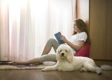 Девушка в ее комнате с собакой стоковое изображение