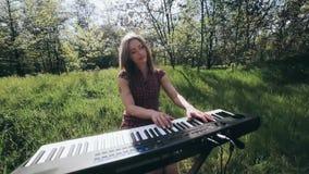 Девушка в лесе играет синтезатор и поет сток-видео