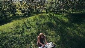 Девушка в лесе играет синтезатор и поет видеоматериал